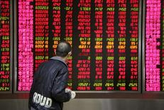 An investor walks past in front of an electronic board showing stock information at a brokerage house in Beijing, China, November 17, 2015. REUTERS/Li Sanxian