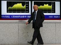 Un hombre camina junto a una pantalla que muestra los datos del mercado, afuera de una correduría en Tokio, 16 de noviembre de 2015. Las bolsas de Asia subían el martes impulsadas por un repunte de Wall Street luego de que disminuyó la inquietud de los inversores sobre los ataques de la semana pasada en París. REUTERS/Thomas Peter