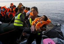 A crying Syrian refugee child is carried by a volunteer after arriving in a raft at a beach on the Greek island of Lesbos, after crossing a part of the Aegean Sea from the Turkish coast, October 20, 2015.   REUTERS/Yannis Behrakis