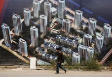 Un hombre camina junto a un muro de un sitio donde se construye un recinto residencial, en Tianjín, China, 18 de octubre de 2015. Los precios de las viviendas en China aumentaron en octubre por primera vez en más de un año sobre una base anual, lo que sugiere una estabilización del mercado inmobiliario que podría ayudar a reactivar a la economía. REUTERS/Kim Kyung-Hoon