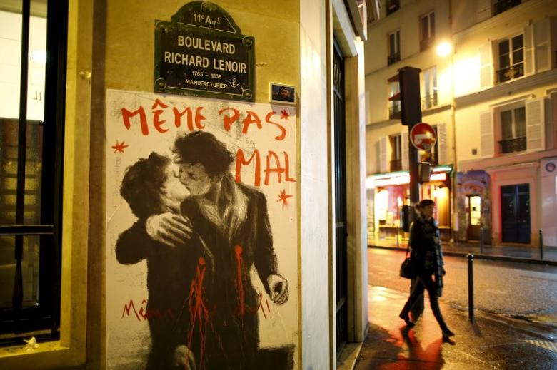 A drawing which reproduces French photographer Robert Doisneau's picture ''Le baiser de l'Hotel de ville'' (Kiss by the Town Hall) with the words ''Not even hurt'' over it, is seen on a wall near the Bataclan concert hall in Paris, November 20, 2015. REUTERS/Charles Platiau