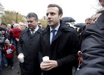 Ministro de Economía de Francia, Emmanuel Macron, y su contraparte de Alemania, Sigmar Gabriel, llevan velas en la Plaza de la República una semana después de los mortales ataques en París, Francia, el 21 de noviembre de 2015. Francia mantendrá sus compromisos financieros, dijo el sábado Macron, después de que París anunció que el aumento del gasto en seguridad tras los ataques del 13 de noviembre en París probablemente hará que el país incumpla las reglas presupuestarias de la Unión Europea.  REUTERS/Eric Gaillard - RTX1V5Q7
