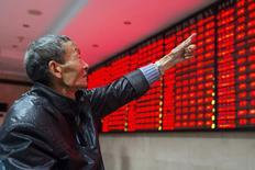 Un inversor apunta a un tablero electrónico que muestra la información de las acciones, en una correduría en Nanjing, China, 19 de noviembre de 2015. Las acciones chinas cerraron a la baja el lunes, y el sector de las telecomunicaciones lideró los descensos en medio de la cautela de los inversores antes de una nueva serie de salidas a bolsa. REUTERS/China Daily