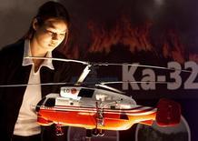 Посетитель выставки Heli-Asia рассматривает модель вертолета KA-32. Куала-Лумпур, 22 октября 2002 года. Входящий в Ростех холдинг Вертолеты России договорился с китайской Jiangsu Baoli о поставке четырех вертолетов Ка-32А11ВС в противопожарном варианте, говорится в сообщении холдинга в понедельник. REUTERS/Zainal Abd Halim