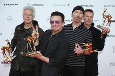 Adam Clayton, Bono, the Edge and Larry Mullen (L-R) of the band U2 pose with their Music International trophies during the Bambi 2014 media awards ceremony in Berlin in this November 13, 2014 file photo.  REUTERS/Hannibal Hanschke/Files