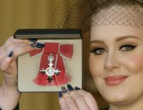 Cantora Adele mostra condecoração recebida por ela no Palácio de Buckingham, em Londres. 19/12/2013  REUTERS/Pool/John Stillwell