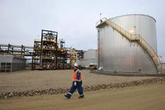An oilfield worker walks past the Statoil oil sands facility near Conklin, Alberta, in this November 3, 2011 file photo.   REUTERS/Todd Korol/Files