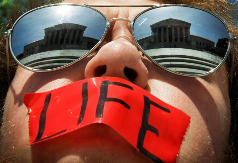 Anti-abortion activist Craig Kuhns wears mirrored sunglasses and a piece of tape over his mouth as he stands in front of the US Supreme Court building in Washington, in this June 1, 2009 file photo. REUTERS/Jonathan Ernst/Files