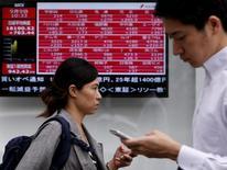 Peatones caminan junto a un tablero electrónico que muestra varios índices de precios, afuera de una correduría en Tokio, Japón, 9 de septiembre de 2015. Las bolsas de Asia caían el martes luego de que una mega fusión en el sector farmacéutico no logró impresionar a Wall Street, y el dólar hacía una pausa en su avance a máximos en ocho meses por la convicción de que la Reserva Federal de Estados Unidos subirá las tasas de interés en diciembre. REUTERS/Yuya Shino