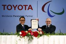 President of the Toyota Motor Corporation Akio Toyoda (L) and President of the International Paralympic Committee Sir Philip Craven hold a contract after they signed a partnership deal in Tokyo, November 26, 2015. REUTERS/Thomas Peter