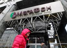 People pass by a MegaFon office in Moscow, November 26, 2012. MegaFon, Russia's No.2 mobile phone firm, pitched its $2 billion international stock market float to Moscow-based investors on Friday, amid indications that efforts to fill the order book would go down to the wire. Sources close to the offering said the final takeup of shares in MegaFon, controlled by Russia's richest man Alisher Usmanov, would only be clear early this week after U.S. investors return from the long Thanksgiving weekend. REUTERS/Maxim Shemetov (RUSSIA - Tags: BUSINESS TELECOMS) - RTR3AWA2