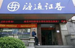 Foto de archivo de un hombre fumando en la entrada de una correduría de Haitong Securities, en Shanghái, 27 de abril de 2012. Haitong Securities está siendo investigada por la Comisión Reguladora de Valores de China (CSRC, por su sigla en inglés), dijeron el viernes a Reuters dos personas con conocimiento directo del asunto, tras investigaciones similares a otras dos corredurías nacionales. REUTERS/Aly Song/Files