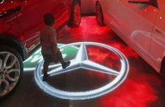 A boy walks past a Mercedes Benz logo on an electronic board at Colombo motor show October 16, 2014. REUTERS/Dinuka Liyanawatte/Files