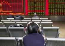 Un inversor sentado frente a un tablero electrónico que muestra la información de las acciones, en una correduría en Pekín, China, 30 de noviembre de 2015. Las acciones chinas cerraron estables tras de una sesión volátil en la que los principales índices entraron y salieron de territorio negativo luego de la caída del viernes de más de un 5 por ciento. REUTERS/Li Sanxian