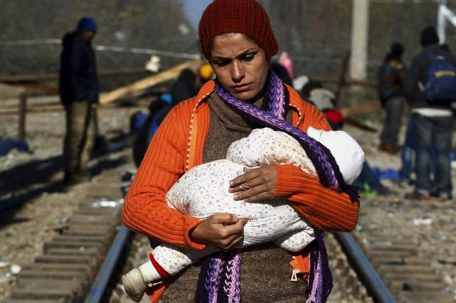 A stranded migrant holds a baby as she waits next to the Greek-Macedonian border near to the Greek village of Idomeni, November 30, 2015. REUTERS/Alexandros Avramidis