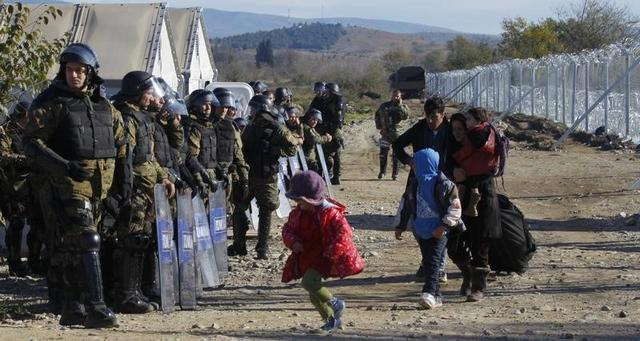 Migrants walks past Macedonian police after crossing the Macedonian-Greek border, near Gevgelija, Macedonia, November 30, 2015. REUTERS/Ognen Teofilovski
