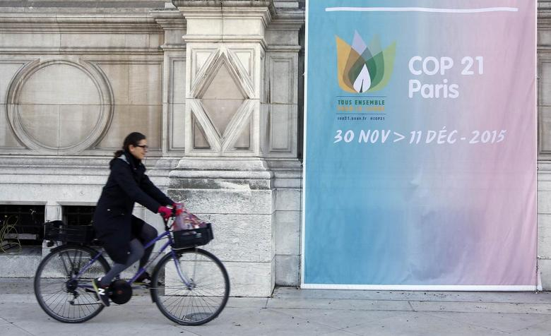 A woman cycles past a poster for the COP21 World Climate Summit, in front of Paris hall city, France, November 26, 2015.   REUTERS/Eric Gaillard