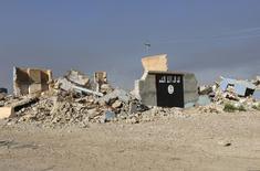 Los restos de una muralla pintada con la bandera del Estado Islámico en al-Alam, Iraq, mar 10, 2015. Un video publicado el miércoles en internet por Estado Islámico parece mostrar la decapitación de un hombre identificado por el grupo como un espía ruso capturado por sus combatientes y que se encontraba en Siria e Irak desde el año pasado, informó el grupo de análisis de seguridad SITE.  REUTERS/Thaier Al-Sudani