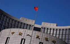Una bandera china ondea afuera de la sede del Banco Central de China, en Pekín, 3 de abril de 2014. Un funcionario del banco central chino dijo el viernes que la inclusión del yuan en la canasta referencial de monedas del Fondo Monetario Internacional, conocida como Derechos Especiales de Giro (DEG), sería un punto de partida para las reformas financieras de China. REUTERS/Petar Kujundzic