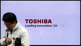 Un hombre pasa delante de un logo de Toshiba Corp en Tokio, Japón, 26 de noviembre de 2015. Las empresas japonesas Toshiba Corp y Fujitsu Ltd están en conversaciones para fusionar sus filiales de computadoras personales, dijeron personas familiarizadas con el asunto, en línea con sus estrategias de retirarse de negocios deficitarios. REUTERS/Toru Hanai
