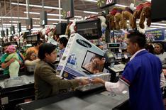 Una persona pagando por sus compras en un supermercado de la cadena WalMart en Ciudad de México, nov 17, 2011. La confianza de los consumidores de México creció en noviembre frente al mes anterior, principalmente por una mejor percepción sobre la situación económica actual comparada con la de hace doce meses, dijo el viernes el instituto nacional de estadísticas, INEGI.   REUTERS/Henry Romero