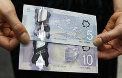 The Canadian five and 10 dollar bills, made of polymer, are displayed following an unveiling ceremony at the Bank of Canada in Ottawa April 30, 2013.     REUTERS/Chris Wattie