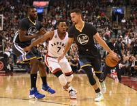 Dec 5, 2015; Toronto, Ontario, CAN;  Golden State Warriors guard Stephen Curry (30) dribbles past Toronto Raptors guard Kyle Lowry (7) and Warriors center Festus Ezeli (31) in the second quarter at Air Canada Centre. Mandatory Credit: Dan Hamilton-USA TODAY Sports