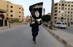 """Член ИГИЛ с флагом в Ракке 29 июня 2014 года. Россиянин, обезглавленный """"Исламским государством"""" за шпионаж, пресекал попытки исламистов завербовать его для участия в войне на Ближнем Востоке, рассказала в пятницу Рейтер его приемная семья. REUTERS/Stringer"""