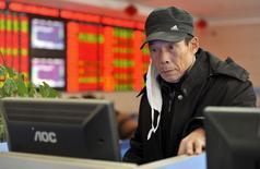 Инвестор в брокерской фирме в Фуяне, Китай 1 декабря 2015 года. Китайские акции выросли в понедельник, так как инвесторы переключились с риэлторских компаний на сферы технологий и здравоохранения, которые Пекин рассчитывает сделать новыми драйверами роста. REUTERS/Stringer