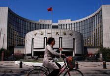 Una mujer en bicicleta pasa junto a la sede del Banco Central de China, en Pekín, 3 de abril de 2014. Las reservas de divisas de China, las más grandes del mundo, cayeron en 87.200 millones de dólares en noviembre a 3,44 billones de dólares, mostraron el lunes datos del banco central. REUTERS/Petar Kujundzic