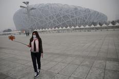 """Женщина в защитной маске делает селфи у Национального стадиона в Пекине. 8 декабря 2015 года. Смог может продержаться в Пекине не менее трех дней из-за влажной, безветренной погоды, в результате чего во вторник в китайской столице был впервые объявлен """"красный код"""" опасности. REUTERS/Damir Sagolj"""