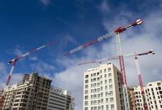 El precio de la vivienda en España subió un 4,5 por ciento interanual en el tercer trimestre de 2015, lo que supone su mayor aumento desde el cuarto trimestre de 2007, según los datos publicados el jueves por el Instituto Nacional de Estadística (INE).  En la imagen, varias grúas sobre un bloque de viviendas a las afueras de Madrid en enero de 2014.  REUTERS/Paul Hanna