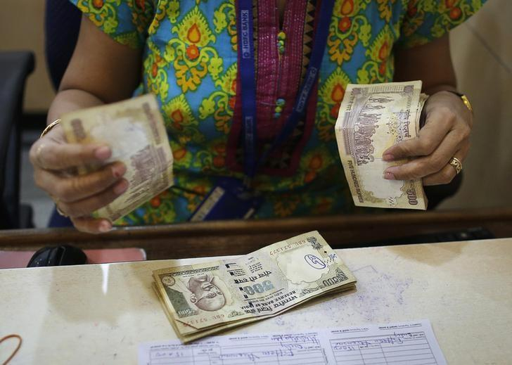A cashier counts rupee currency notes inside a bank in Mumbai December 6, 2013. REUTERS/Danish Siddiqui/fILES