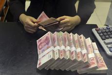 Un trabajador cuenta billetes de 100 yuanes, en una sucursal de China Merchants Bank, en Hefei, China, 20 de abril de 2015. El yuan chino caía a 6,4520 unidades por dólar en el comercio de la mañana del viernes, su nivel más bajo en casi cuatro años y medio, lo que plantea interrogantes sobre cuánto permitirá Pekín que la moneda se debilite. REUTERS/Stringer