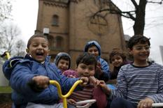 Migrant children from Syria pose in front of a Protestant church in Oberhausen, Germany, November 19, 2015. REUTERS/Ina Fassbender