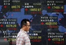 Un hombre camina junto a un tablero electrónico que muestra la información de las acciones, afuera de una correduría en Tokio, Japón, 23 de octubre de 2015. Las bolsas de Asia se encaminaban el viernes a unas pérdidas semanales, en momentos en que la caída de los precios del crudo y un desplome del yuan chino a un mínimo en casi cuatro años y medio aumentaban las preocupaciones acerca de un apagado crecimiento mundial. REUTERS/Toru Hanai