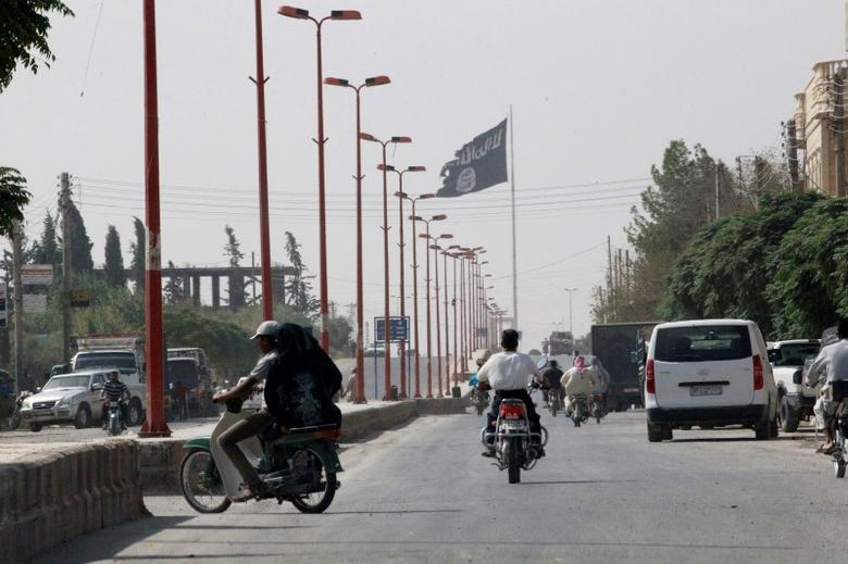 Residents drive across a street with a fluttering Islamic State flag, in Tel Abyad town on the Syrian-Turkish border, Raqqa countryside September 24, 2014.  REUTERS/Stringer