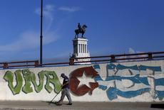 Cuba alcanzó un acuerdo con sus acreedores bajo el cual le condonarán 4.000 millones de dólares en cargos por atrasos en los pagos y La Habana devolverá 2.600 millones de dólares adeudados en un plazo de 18 años, dijo el sábado el ministro de Finanzas de Francia, Michel Sapin. En la imagen de archivo, un hombre barre una acera junto a un grafiti en Cuba, el 19 de septiembre de 2015/REUTERS