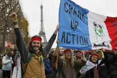"Environmentalists hold a banner which reads, ""Crank up the Action"" at a protest demonstration near the Eiffel Tower in Paris, France, as the World Climate Change Conference 2015 (COP21) continues near the French capital in Le Bourget, December 12, 2015.   REUTERS/Mal Langsdon  - RTX1YD4F"