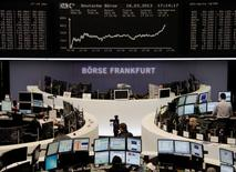 Traders work at their desks in front of the DAX board at the Frankfurt stock exchange March 18, 2013.  REUTERS/Remote/Janine Eggert