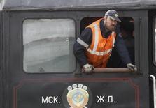 Техник выглядывает из локомотива в Музее железнодорожного транспорта в Москве. 1 июля 2012 года. Минэкономразвития РФ считает, что после недавней смены главы железнодорожной монополии не нужно торопиться с либерализацией локомотивного рынка. REUTERS/Sergei Karpukhin