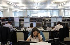 Трейдеры в торговом зале инвестбанка Ренессанс Капитала в Москве. 9 августа 2011 года. Российские фондовые индексы балансируют в среду в районе положительных значений на низких оборотах, а лучше рынка выглядят акции отчитавшейся накануне Русгидро. REUTERS/Denis Sinyakov