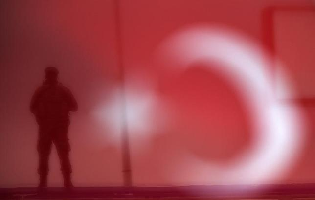 A soldier is seen through a Turkish national flag as he stands guard during an AK Party election rally in Diyarbakir, Turkey October 29, 2015. REUTERS/Stoyan Nenov/Files