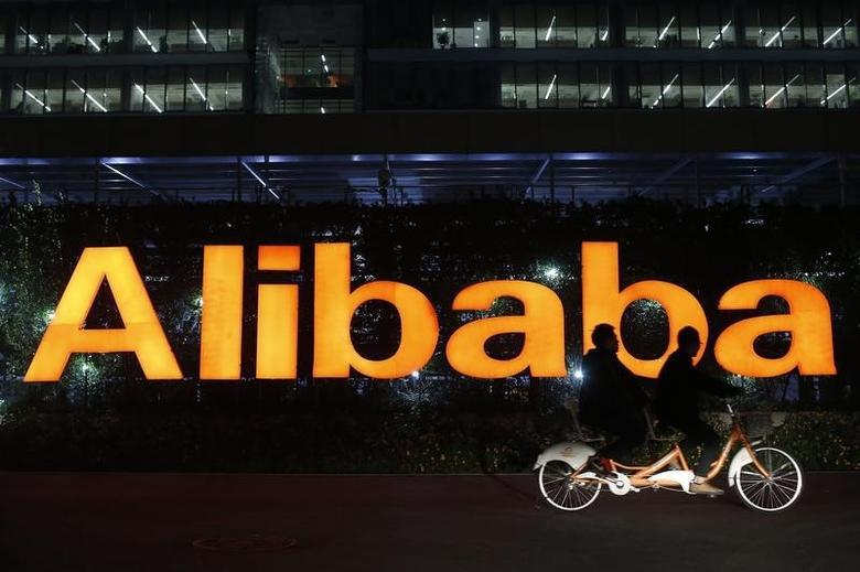 People ride a double bicycle past a logo of The Alibaba Group at the company's headquarters on the outskirts of Hangzhou, Zhejiang province November 10, 2014.  REUTERS/Aly Song/Files