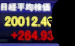 Un hombre mira un tablero electrónico que muestra el índice Nikkei de Japón, afuera de una correduría en Tokio, 1 de diciembre de 2015. Las acciones japonesas cayeron el viernes en una sesión que se volvió volátil después que el Banco de Japón anunció que mantendría su objetivo de base monetaria bajo su programa de estímulo, al tiempo que amplió los tipos de activos que compra. REUTERS/Toru Hanai