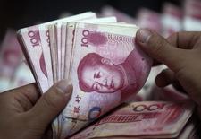 Un empleado bancario cuenta billetes de 100 yuanes chinos, en una sucursal del Industrial and Commercial Bank of China, en Huaibei, provincia de Anhui, 8 de junio de 2012. China flexibilizará su política monetaria el próximo año a fin de recrear las condiciones apropiadas para las reformas estructurales, al tiempo que expande el déficit presupuestario, dijo el lunes la agencia de noticias Xinhua, citando decisiones que se tomaron en un encuentro de alto nivel. REUTERS/Stringer