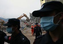 Полицейские охраняют индустриальный парк, на который обрушился оползень, в Шэньчжэне. 22 декабря 2015 года. Китайская полиция провела обыски в офисах компании-оператора, отвечающей за свалку, на месте которой произошел гигантский оползень. REUTERS/Kim Kyung-Hoon