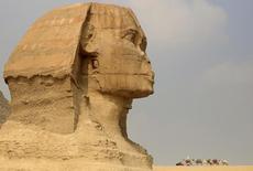 Работник индустрии развлечений ждет туристов, сидя на верблюде рядом со Сфинксом в египетских пирамидах под Каиром 8 ноября 2015 года.Власти Египта наняли международную консалтинговую фирму Control Risks для оценки безопасности в ряде аэропортов после крушения российского самолёта на Синайском полуострове, сообщил во вторник министр туризма Хишам Заазу. REUTERS/Amr Abdallah Dalsh