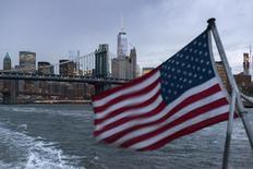 Vista de una bandera de Estados Unidos con el Puente de Manhattan y el One World Trade Center, en Nueva York, 21 de septiembre de 2015. La economía de Estados Unidos creció a un ritmo bastante saludable en el tercer trimestre pues la solidez del consumo y la inversión empresarial contrarrestaron los esfuerzos de las empresas para reducir un exceso de inventarios, subrayando su resistencia pese a una serie de factores en contra. REUTERS/Darren Ornitz