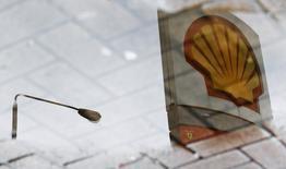 Royal Dutch Shell a de nouveau réduit jeudi ses projets d'investissements pour 2016, de deux milliards de dollars à 33 milliards (30 milliards d'euros), au vu de la glissade des cours de pétrole. /Photo d'archives/REUTERS/Luke Macgregor